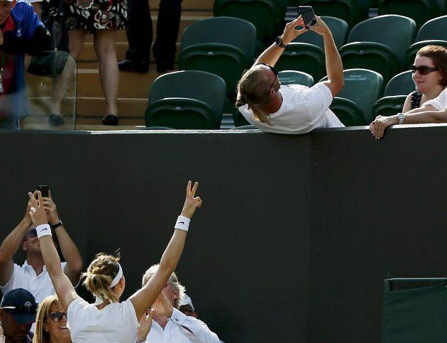 Lucie Šafářová pózuje na kurtu pod tribunou s roztaženými pažemi a širokým úsměvem pro selfie fotku trenéra Roba Steckleyho.
