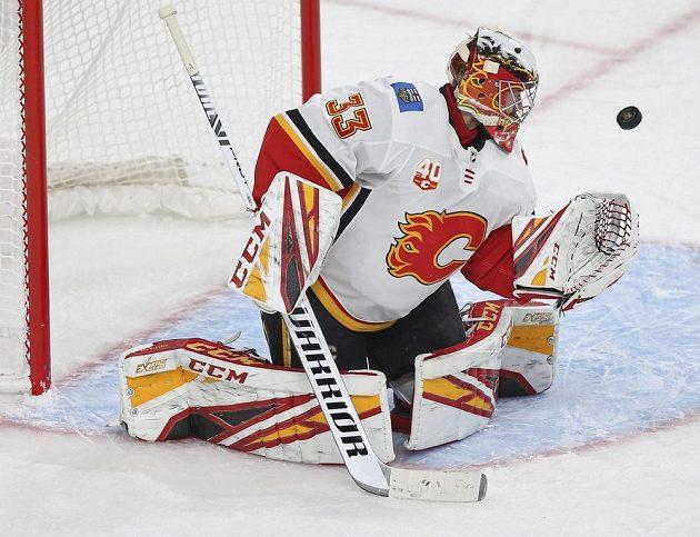 Gólman Calgary Flames David Rittich zasahuje během utkání NHL.