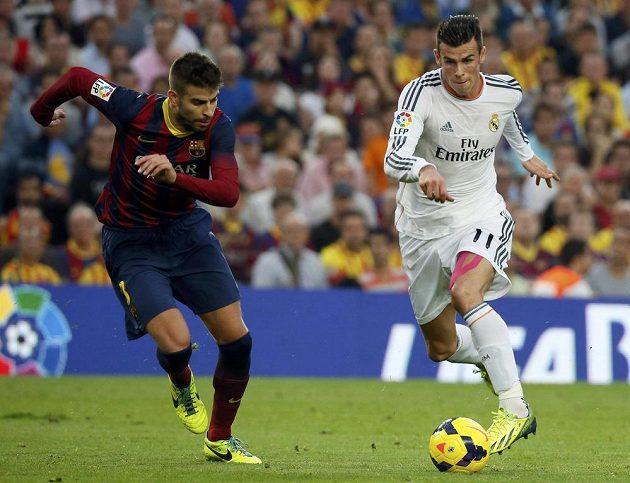 Hvězda Realu Gareth Bale (v bílém) ve sprinterském souboji s obráncem Barcelony Gerardem Piquém.