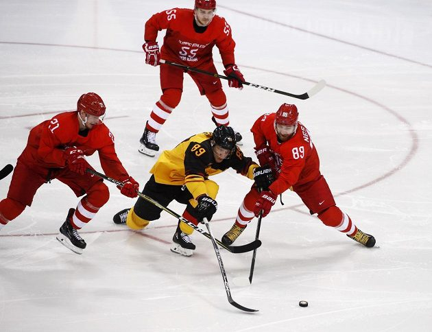 Německý hokejista David Wolf v olympijském finále proti sborné. Na snímku v dresu OSR Nikita Nestěrov (89), Sergej Kalinin (21). V první třetině se ujal výběr OSR vedení 1:0.