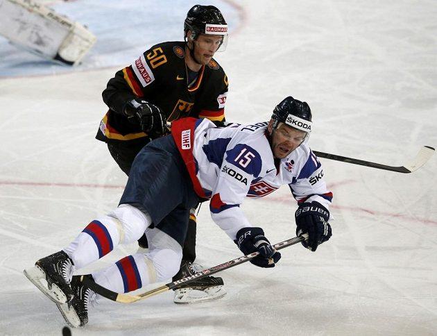 Slovenský útočník Jozef Stümpel v souboji s německým forvardem Patrickem Hagerem v utkání mistrovství světa v ledním hokeji.