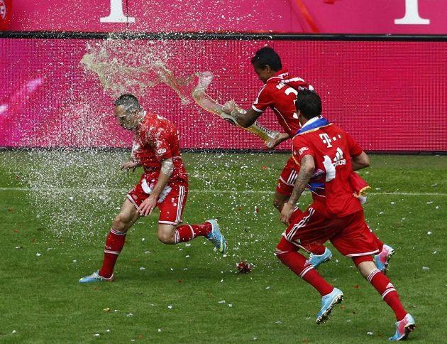 Francka Ribéryho (vlevo) polívá pivem spoluhráč z Bayernu Mnichov Luiz Gustavo (uprostřed). Vpravo přihlíží Mario Manžukič.