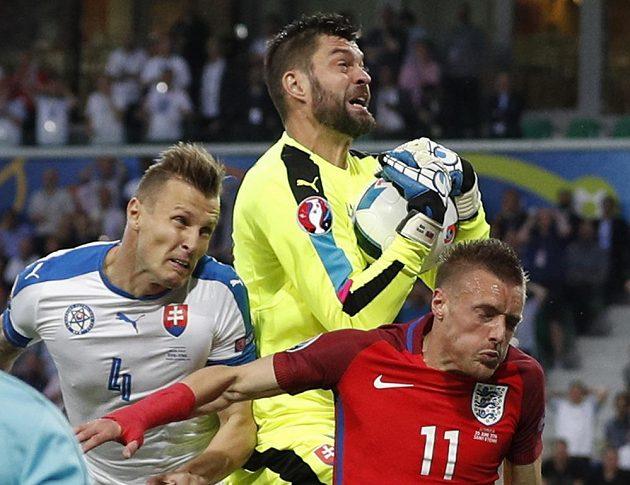 Slovenský brankář Matúš Kozáčik drží míč, vlevo Ján Ďurica, vpravo Jamie Vardy.