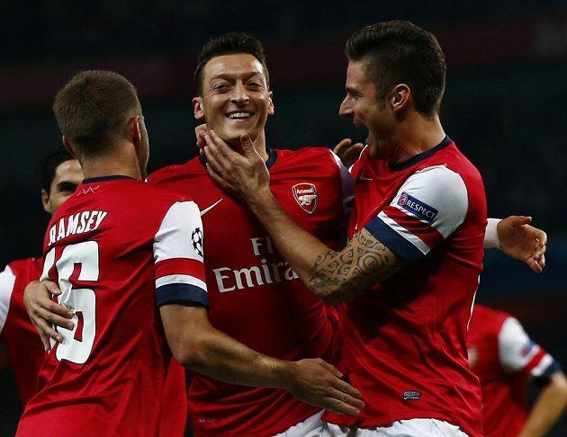 Mesut Özil (uprostřed), autor úvodní trefy Arsenalu v duelu Ligy mistrů s Neapolí, oslavuje gól se spoluhráči Aaronem Ramseym a Olivierem Giroudem (vpravo).