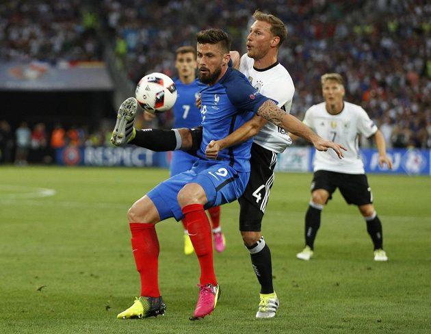 Francouz Olivier Giroud (vlevo) si kryje míč před Němcem Benediktem Höwedesem.