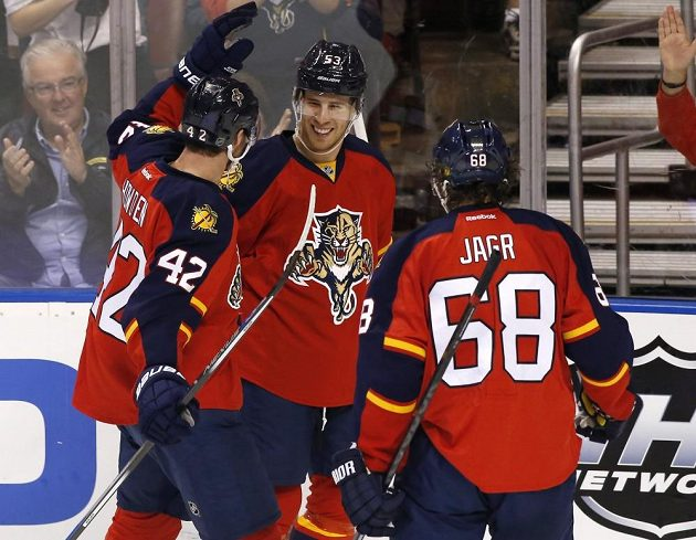 Hokejisté Floridy Quinton Howden (vlevo) a Jaromír Jágr (vpravo) se radují se střelcem gólu Corbanem Knightem.