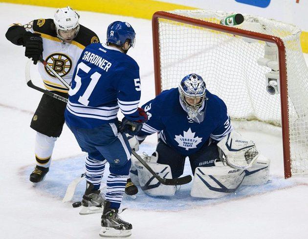Útočník Bostonu Jaromír Jágr (vlevo) v souboji s obráncem Toronta Jakem Gardinerem. Vpravo brankář Maple Leafs James Reimer.