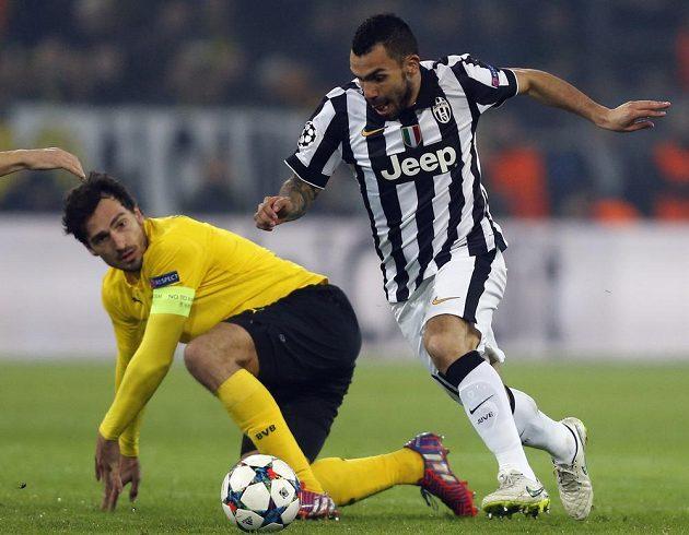 Hvězda Juventusu Turín Carlos Tévez obchází kapitána Dortmundu Mattse Hummelse.
