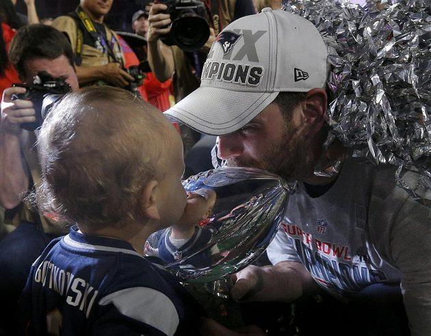 Stephen Gostkowski z vítězného týmu líbá trofej pro vítěze Super Bowlu společně se svým nejmladším synem.