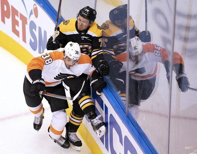 Útočník hokejové Philadelphie Flyers Derek Grant (38) čelí ataku obránce Bostonu Bruins Jeremyho Lauzona (79).