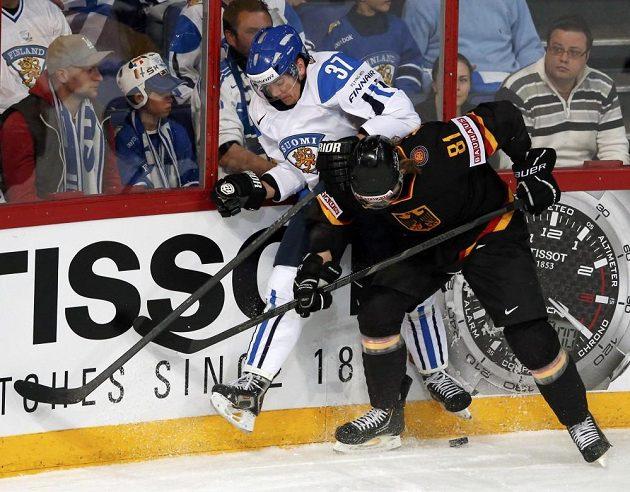 Německý hokejista Torsten Ankert v souboji u mantinelu s Finem Juha-Pekkou Haatajou.