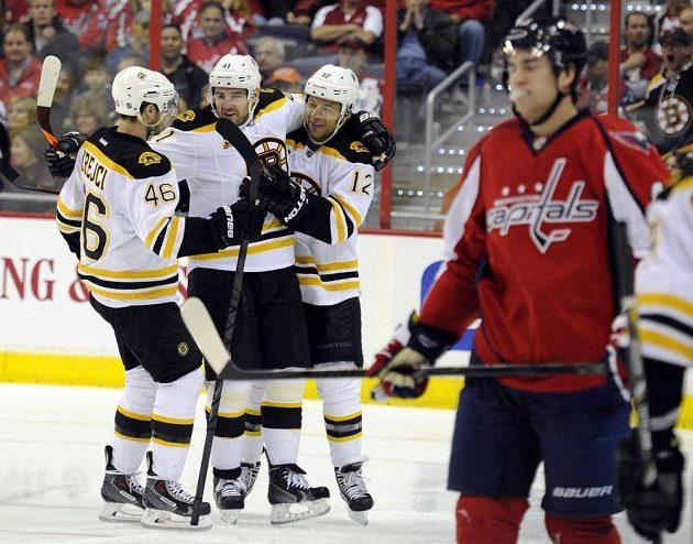 Bostonský Jarome Iginla (12) během druhé třetiny proti Washingtonu slaví gól s Davidem Krejčím (46) a Andrejem Meszarosem (41).