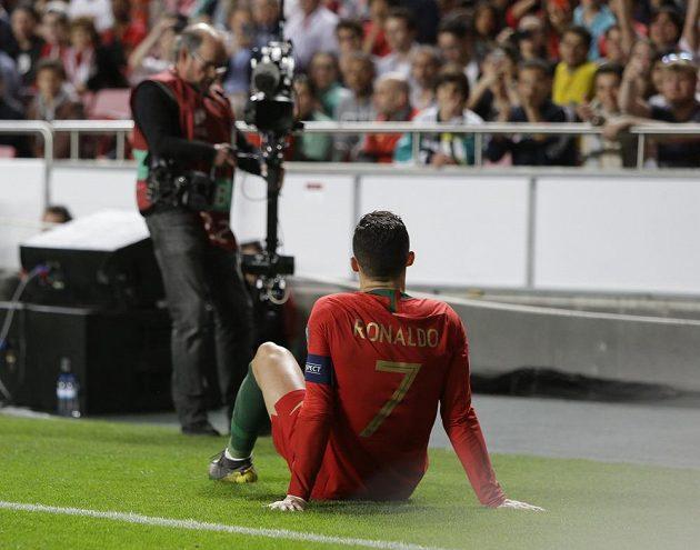 Zraněný Cristiano Ronaldo sedí na zemi během kvalifikačního duelu se Srbskem.