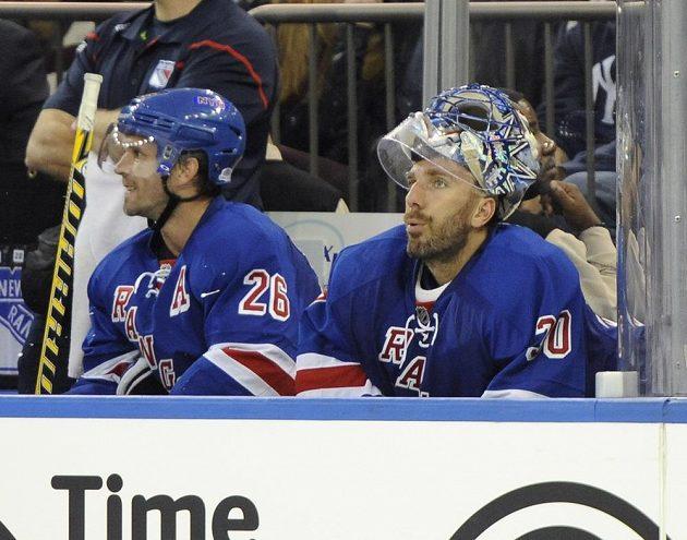 Tohle se brankářské opoře New Yorku Rangers Henriku Lundqvistovi (vpravo) příliš často nestává. Na snímku sedí vedle Martina St. Louise poté, co jej ve druhé třetině duelu NHL vyhnali na střídačku střelci Toronta.