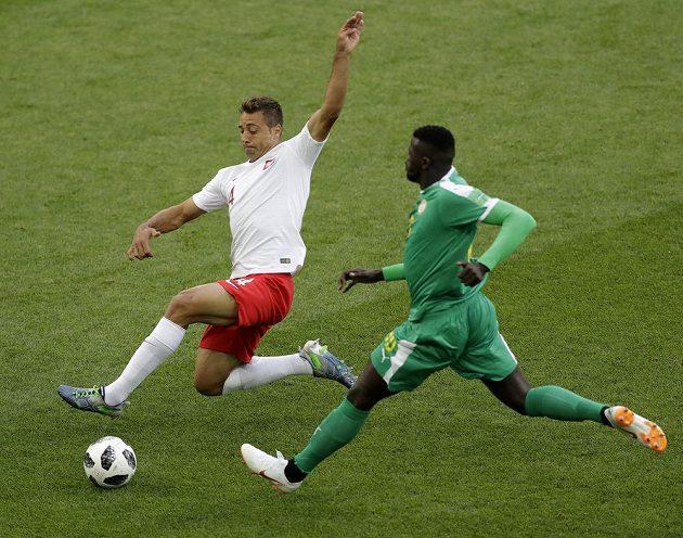 Polský fotbalový reprezentant Thiago Cionek se snaží zastavit během utkání MS Senegalce Ismaila Sarra.