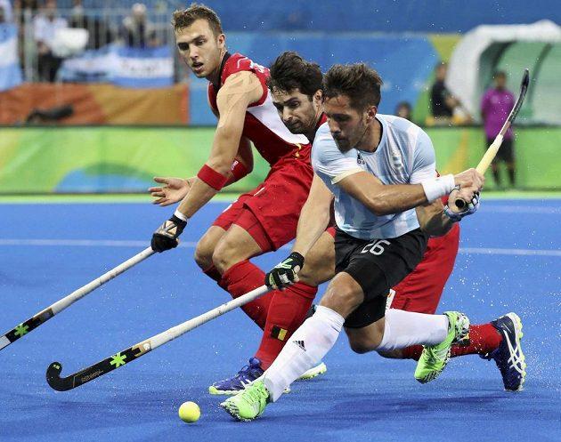 Agustin Mazzilli proti dvojici belgických pozemních hokejistů Loick Luypaert (uprostřed) a Manu Stockbroekx.
