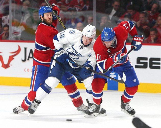 Ondřej Palát (18) se snaží projít přes dvojici hokejistů Montrealu Torreyho Mitchella (17) a Brandona Prusta.