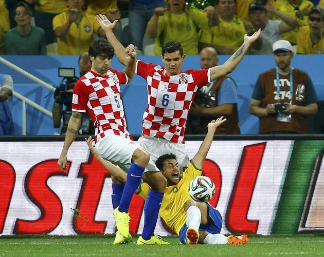 Brazilec Fred (ve žlutém dresu) se ocitá na zemi po souboji s obráncem Dejanem Lovrenem (vpravo).