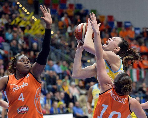 Basketbalistka USK Anete Steinbergaová se snaží prosadit mezi dvojicí hráček ze Schia. Vlevo je Isabelle Yacoubouvá, vpravo pak Jolene Andersonová.