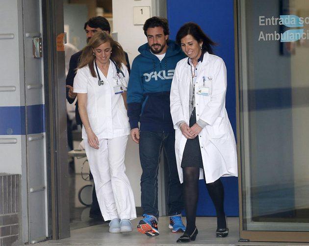 Pilot F1 Fernando Alonso při odchodu z nemocnice v Barceloně.