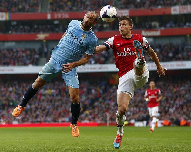 Útočník Arsenalu Olivier Giroud (vpravo) v souboji o míč s Pablem Zabaletou z Manchesteru City.