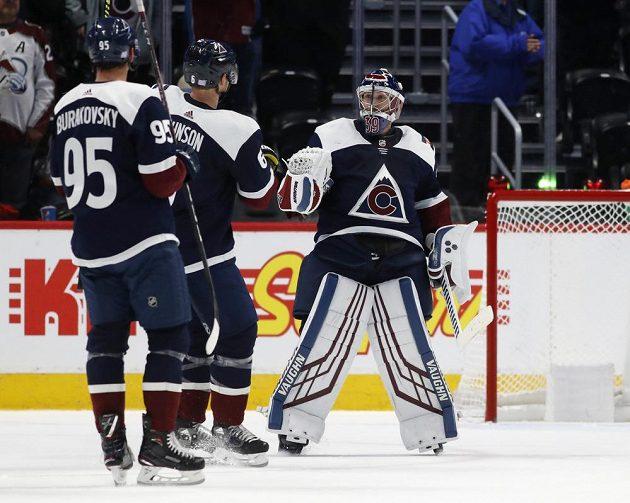 Hokejisté Colorada Avalanche André Burakovsky a Erik Johnson gratulují po vítězném utkání v NHL brankáří Pavlu Francouzovi.