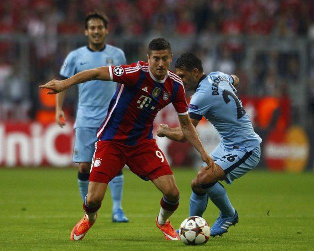 Útočník fotbalistů Bayernu Robert Lewandowski uniká stoperovi Manchesteru City Martínovi Demichelisovi.