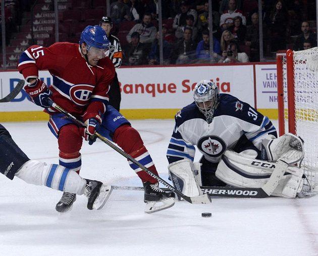 Gólman Winnipegu Ondřej Pavelec (31) zastavuje akci montrealského Tomáše Fleischmanna (15) ve třetí třetině.