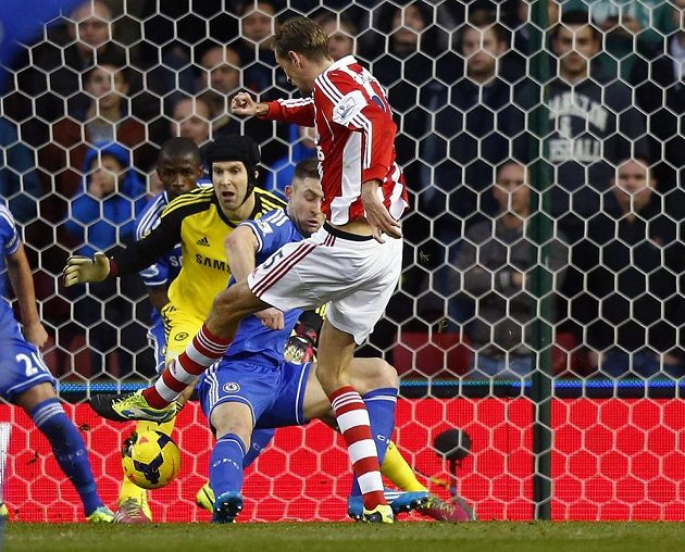 Útočník Stoke City Peter Crouch střílí gól brankáři Chelsea Petru Čechovi.