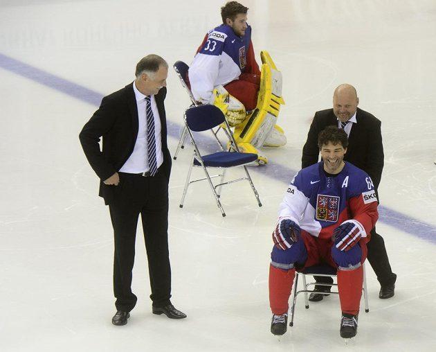 Fyzioterapeut Pavel Kolář (vpravo) odváží na židli Jaromíra Jágra po focení týmu na tréninku. Vlevo je generální manažer týmu Slavomír Lener, druhý zleva brankář Pavel Francouz.