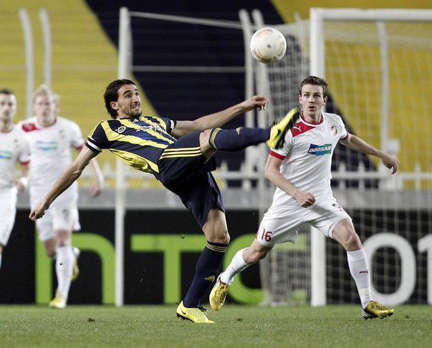 Mehmet Topal z Fenerbahce odkopává míč, vpravo přihlíží plzeňský Vladimír Darida.