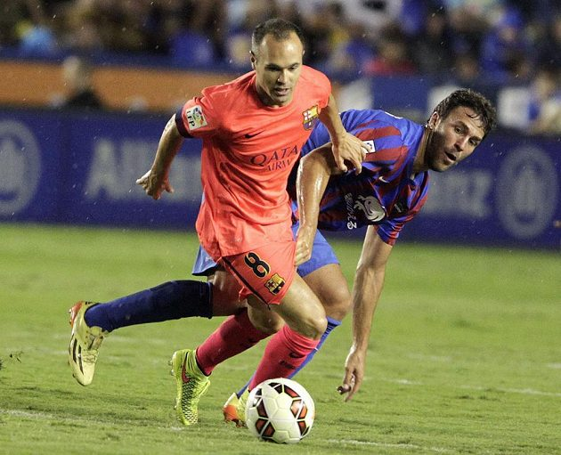 Hector Rodas z Levante (vzadu) se snaží zastavit záložníka Barcelony Andrése Iniestu.