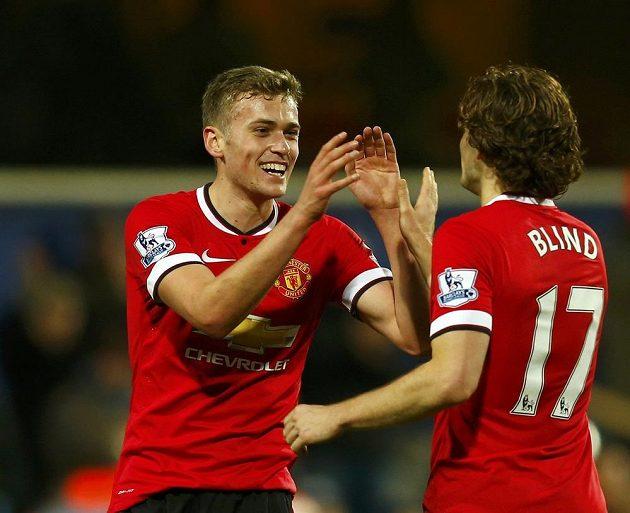 Fotbalisté Manchesteru United James Wilson a Daley Blind se radují z dvoubrankové výhry na Loftus Road proti domácímu Queens Park Rangers.