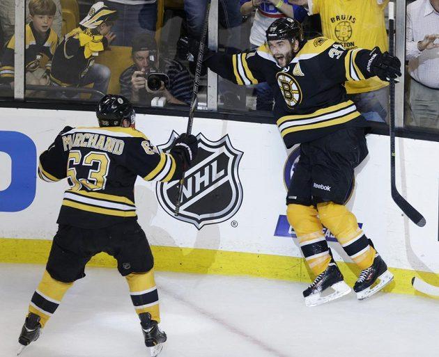 Útočník Bruins Patrice Bergeron (37) a jeho spoluhráč Brad Marchandd (63) slaví vítězný gól Bostonu v třetím zápase proti Pittsburghu Penguins.