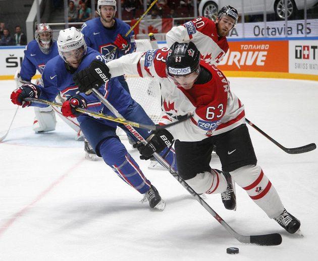 Kanadský hokejista Brad Marchand (63) drží kotouč před bránícím Francouzem Benjaminem Fauvelem.