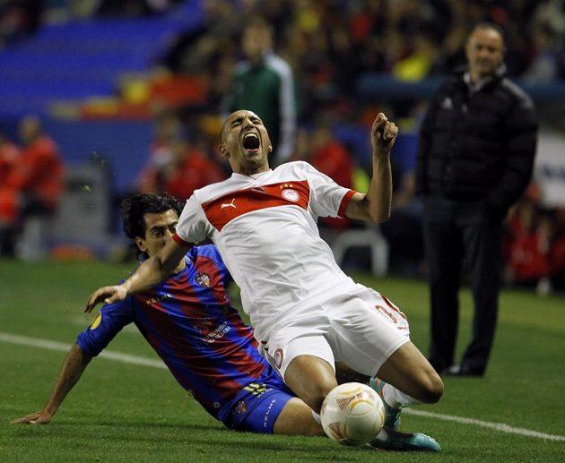 Rafik Djebour (vpředu) z Olympiakosu Pireus padá po zákroku Pedra Riose z Levante.