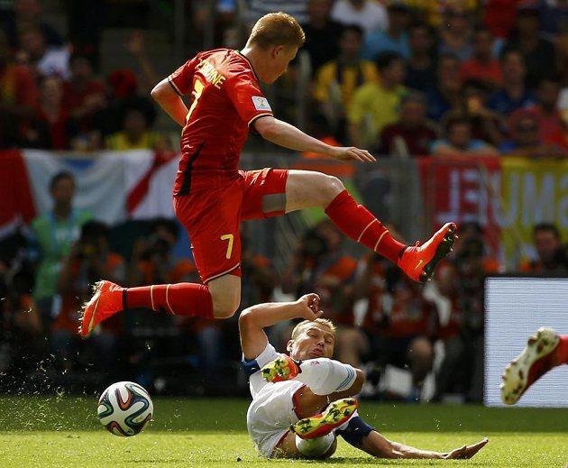 Belgičan De Bruyne přeskakuje Rusa Berezuckého v zápase skupiny H na MS v Brazílii.