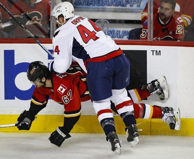 Hokejista Washingtonu Capitals Brooks Orpik (vpravo) při souboji u mantinelu s Michaelem Frolíkem z Calgary.