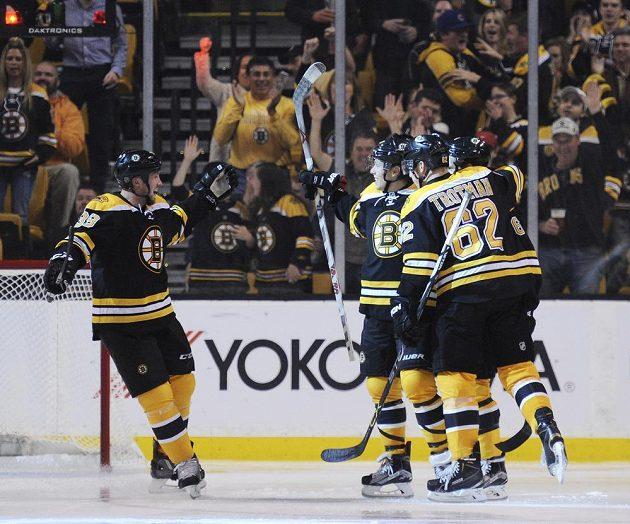 Český hokejista Bostonu David Pastrňák (uprostřed) slaví gól se spoluhráči Zachem Trotmanem (62) a Mattem Beleskeyem proti Winnipegu.