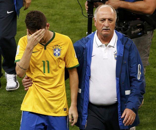 Smutný brazilský záložník Oscar (vlevo) a trenér Luiz Felipe Scolari odcházejí ze hřiště po vysoké porážce s Německem.