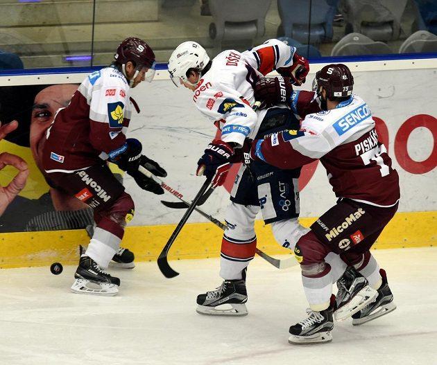 Tomáš Netík (vlevo) a Jan Piskáček (vpravo) ze Sparty a chomutovský Antonín Dušek bojují o kotouč.
