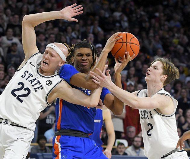 Derrick Alston z Boise State (uprostřed) se snaží dostat ke střele mezi dvěma hráči Utahu.