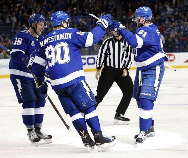Český útočník Ondřej Palát vlevo gratuluje ke gólu střelci Stevenu Stamkosovi v utkání NHL. Z trefy se raduje i jejich spoluhráč Vladislav Namestnikov.