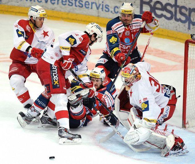 Souboj před brankářem Slavie Praha Dominikem Furchem (vpravo) během utkání předkola play off s Pardubicemi.
