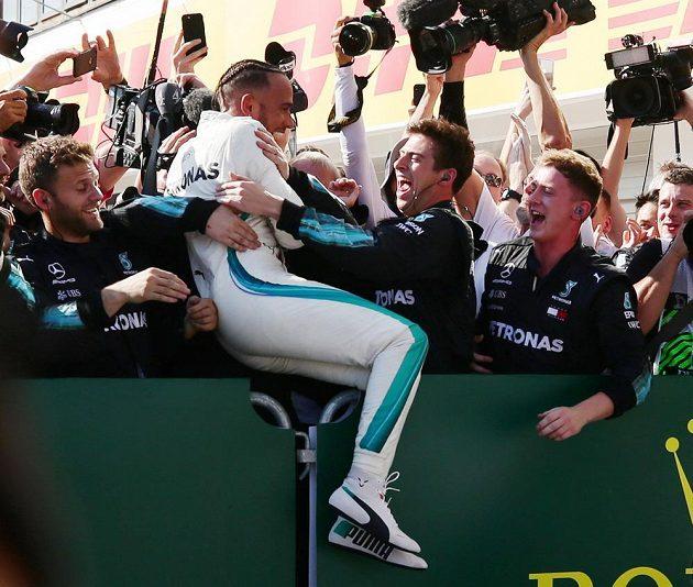 Zase jsem vyhrál! Lewis Hamilton slaví se svým týmem.