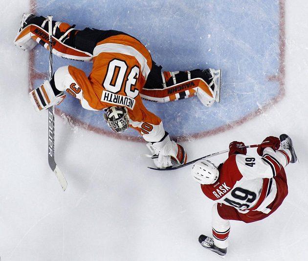 Brankář Philadelphie Flyers Michal Neuvirth (30) kryje střelu Victora Raska (49) z Caroliny.