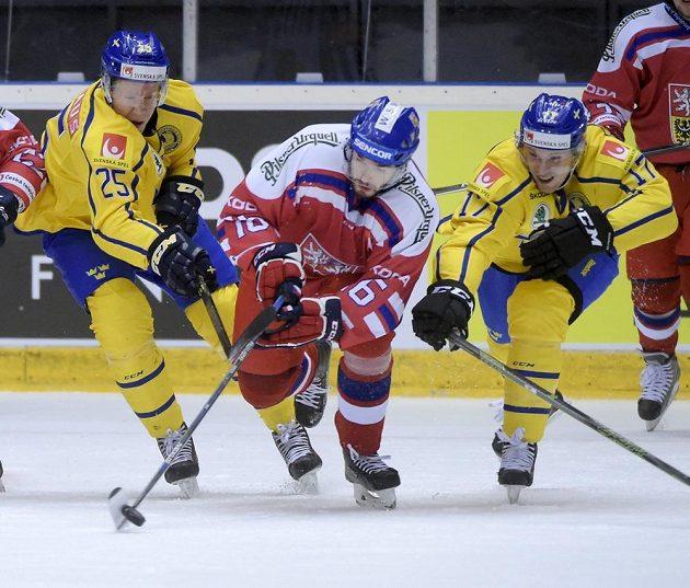 Michal Birner (uprostřed) se snaží dostat puk pod kontrolu, zabránit se mu v tom snaží Švédové Andreas Engqvist (vlevo) a Martin Lundberg.