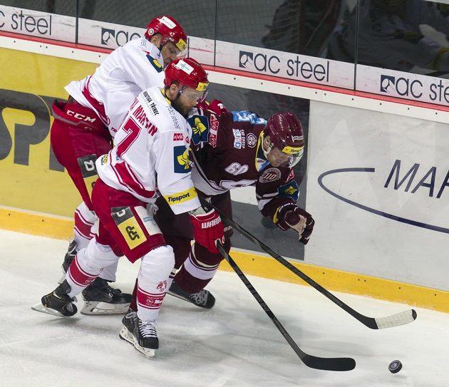 Zleva obránce Lukáš Gavlas a útočník Martin Růžička (oba Třinec) bojují o kotouč se sparťanským útočníkem Tomášem Rolinkem.