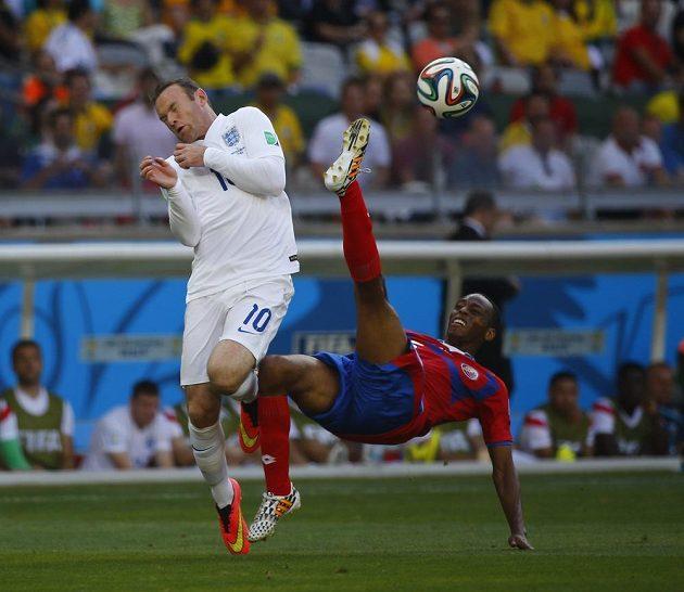 Kostarický obránce Júnior Díaz (vpravo) odkopává akrobaticky míč ve vzduchu před anglickým útočníkem Waynem Rooneym.