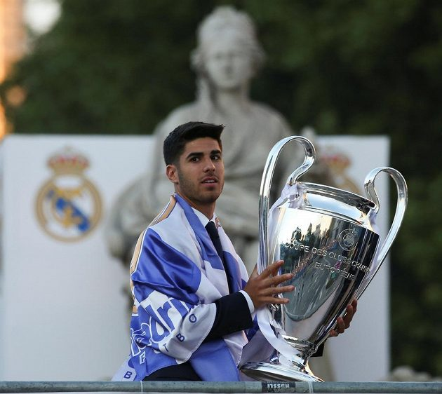 Fotbalista Realu Madrid Asensio slaví s pohárem pro vítěze Ligy mistrů.